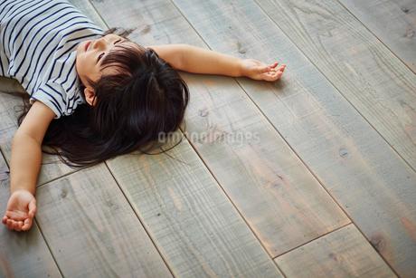 フローリングの床に寝転ぶ女の子の写真素材 [FYI02059822]