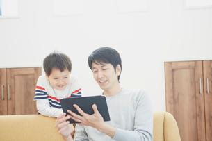 タブレットPCを見る父親と男の子の写真素材 [FYI02059833]