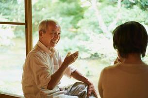 縁側で冷酒を飲むシニア夫婦の写真素材 [FYI02059837]
