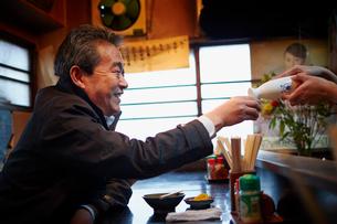 居酒屋で酒を注いでもらう男性客の写真素材 [FYI02059855]
