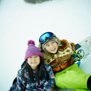 雪の上に座る男の子と女の子とスノーボードの写真素材 [FYI02059856]