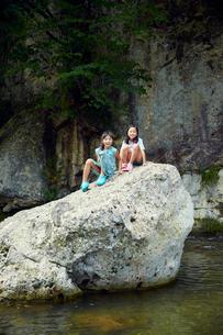 清流の岩の上に座る女の子2人の写真素材 [FYI02059871]