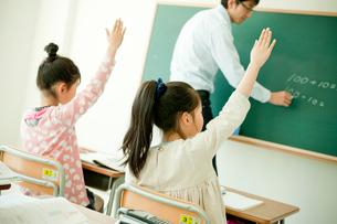 授業中に挙手する小学生の女の子の写真素材 [FYI02059895]