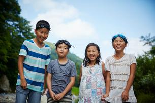 河原に立つ笑顔の子供達の写真素材 [FYI02059898]