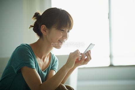 スマートフォンを操作する女性の横顔の写真素材 [FYI02059916]