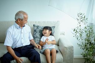 ソファに座る女の子と祖父の写真素材 [FYI02059927]