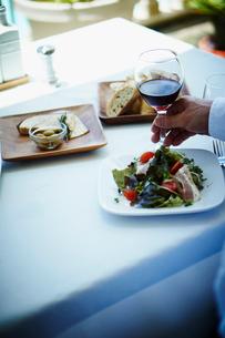 テーブルの上の料理と赤ワイン持つ男性の手の写真素材 [FYI02059948]