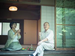 縁側で冷酒を飲みながら庭を眺めるシニア夫婦の写真素材 [FYI02059991]