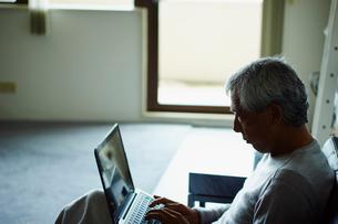 ノートパソコンを操作するシニア男性の写真素材 [FYI02060026]