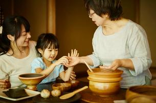 おにぎりを作る三世代女性ファミリーの写真素材 [FYI02060038]