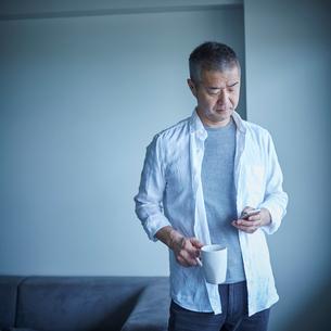 スマートフォンを操作するミドル男性の写真素材 [FYI02060042]