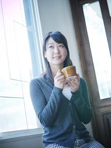 コーヒーカップを持ってくつろぐ女性の写真素材 [FYI02060055]