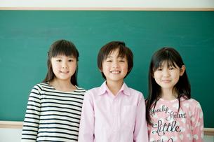 黒板の前に立つ笑顔の小学生3人の写真素材 [FYI02060083]