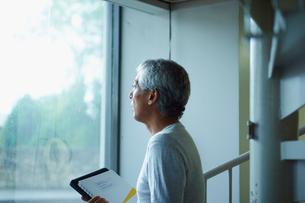 窓の外を眺めるシニア男性の写真素材 [FYI02060160]