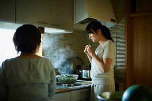 キッチンで枝豆を食べる娘と母親の写真素材 [FYI02060165]