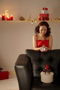 クリスマスプレゼントを見つめる女性の写真素材 [FYI02060180]