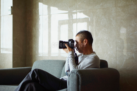 カメラを構えるミドル男性の写真素材 [FYI02060182]