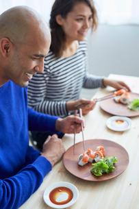 カリフォルニアロールを食べる外国人カップルの写真素材 [FYI02060219]