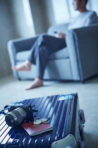 スーツケースとソファに座るミドル男性の写真素材 [FYI02060223]