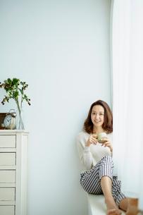 窓辺に座りコーヒーカップを持つ女性の写真素材 [FYI02060232]