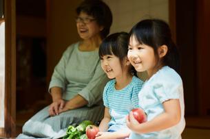 縁側に座る笑顔の祖母と孫の写真素材 [FYI02060234]
