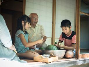 縁側でスイカや野菜を冷やす祖父母と孫たちの写真素材 [FYI02060235]