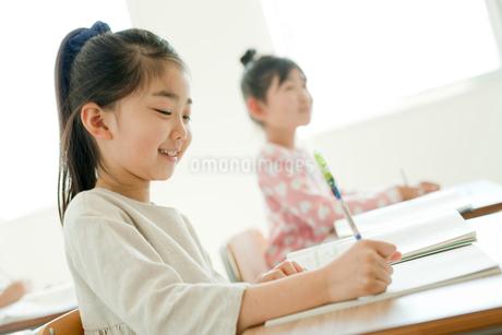 教室で勉強する小学生の女の子2人の写真素材 [FYI02060236]