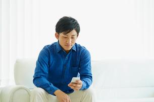 スマートフォンを見る男性の写真素材 [FYI02060245]