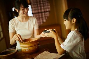 ご飯茶碗を渡す母親と女の子の写真素材 [FYI02060260]