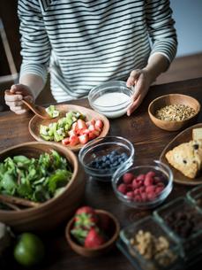 フルーツグラノーラヨーグルトを食べる女性の手元の写真素材 [FYI02060287]