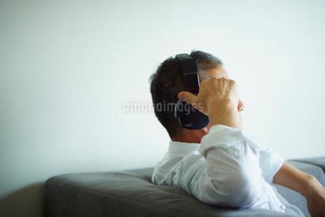 ヘッドフォンで音楽を聴くミドル男性の写真素材 [FYI02060294]