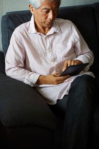 タブレットPCを操作するシニア男性の写真素材 [FYI02060305]