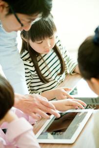 教室で先生と一緒にタブレットPCを操作する小学生の写真素材 [FYI02060313]