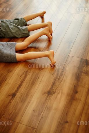 フローリングの床に寝転んだ子供達の足の写真素材 [FYI02060320]