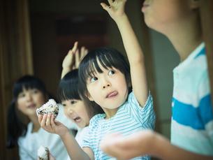 おにぎりを食べながら手を上げる子供たちの写真素材 [FYI02060333]