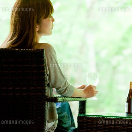 グラスを持ちウッドデッキの椅子に座る女性の後ろ姿の写真素材 [FYI02060335]