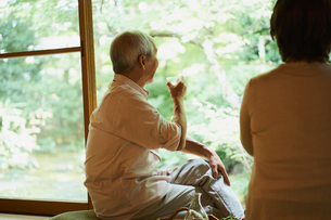 縁側で冷酒を飲むシニア夫婦の写真素材 [FYI02060336]