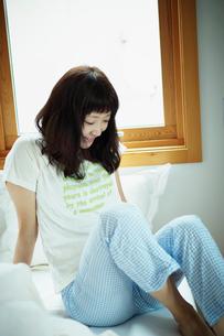 ベッドの上の寝起きの女性の写真素材 [FYI02060344]