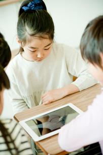 机の上のタブレットPCを見る小学生の写真素材 [FYI02060361]