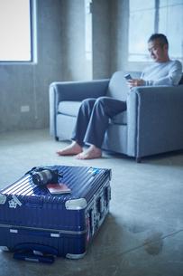 スーツケースとソファに座るミドル男性の写真素材 [FYI02060363]