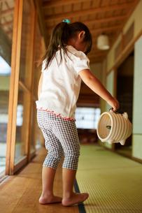 蚊取り豚を持って歩く女の子の写真素材 [FYI02060395]