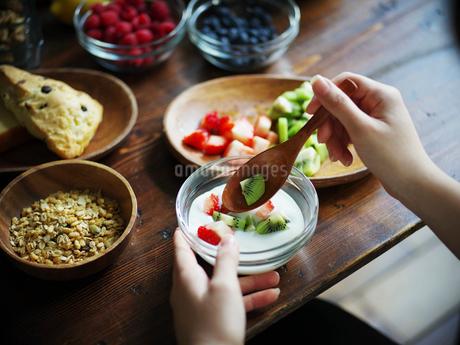 フルーツグラノーラヨーグルトを食べる女性の手元の写真素材 [FYI02060420]