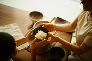ご飯茶碗を渡す母親と女の子の写真素材 [FYI02060435]