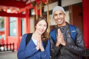 神社で手を合わせる外国人カップルの写真素材 [FYI02060439]