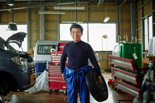 タイヤを持つ笑顔の自動車整備士の写真素材 [FYI02060517]