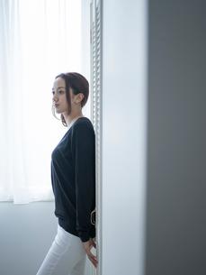 クローゼットのドアに寄りかかる女性の写真素材 [FYI02060534]