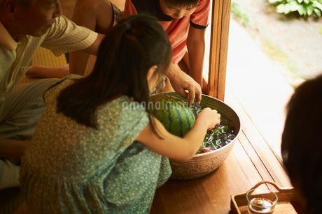 縁側でスイカと野菜を冷やす祖父と孫の写真素材 [FYI02060583]