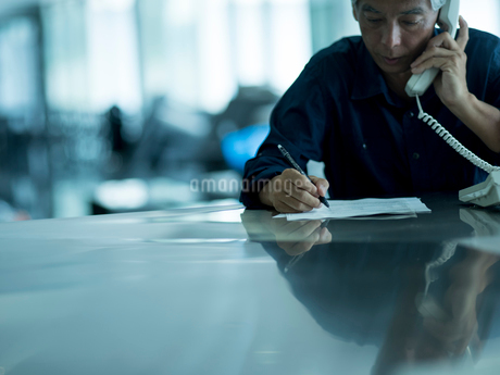 メモしながら電話するシニア男性の写真素材 [FYI02060622]