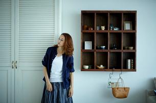 クローゼットの前に立つ女性と壁の棚の写真素材 [FYI02060651]