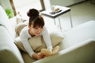 ソファに寝転び本を読む女性の写真素材 [FYI02060659]